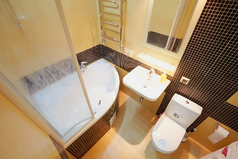 Угловая ванна или душ позволят сэкономить место и увеличить свободное пространство