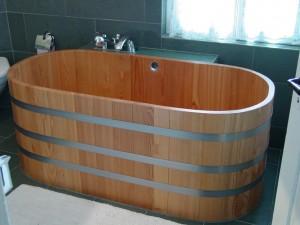 Округлые формы ванны из дерева интересно будут смотреться в просторном помещении и предадут ему неповторимый вид