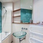 Modern bathroom with green tiles and glass hand wash basin