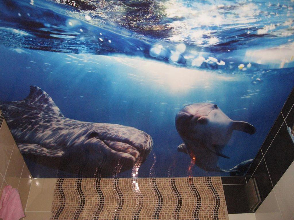 Двухуровневый натяжной потолок в ванной часто украшается узорами морской тематики с пейзажами, пальмами, пляжем